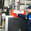 Stock Photo: Heating engineer repairmin boiler room