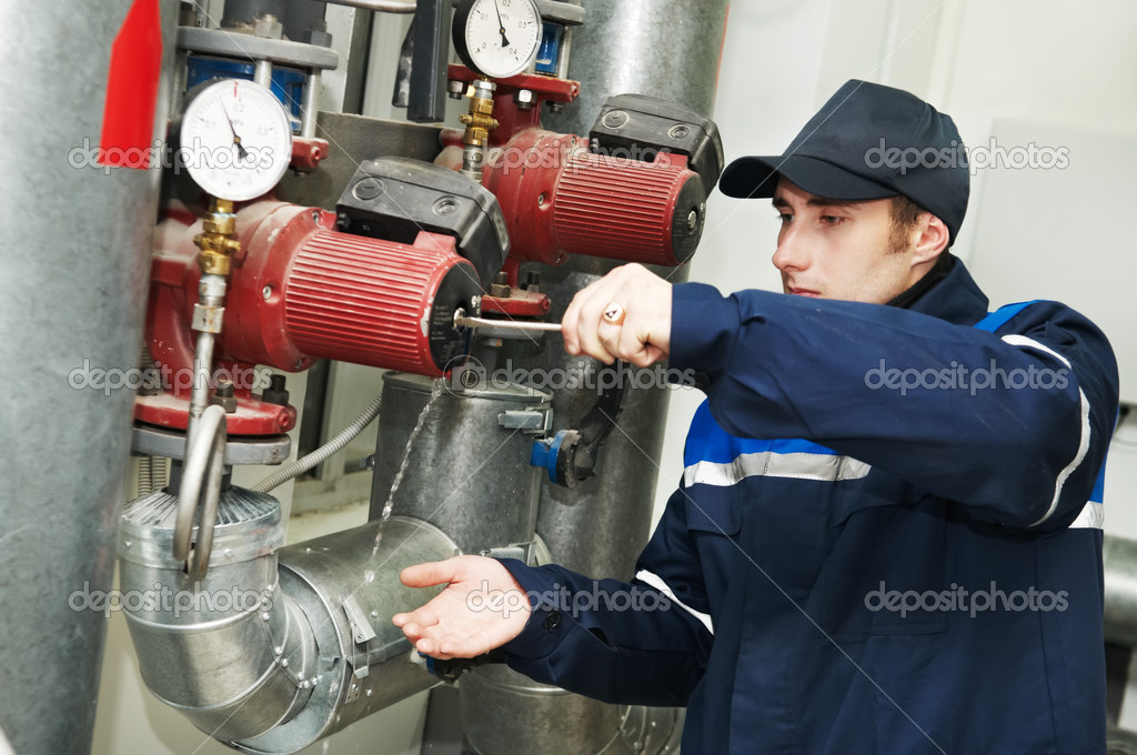 Maintenance engineer repairing water pump of heating system equipment in a boiler house — Stock Photo #6022879