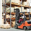 Worker driver at warehouse forklift loader works — Stock Photo #6045138