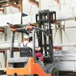 Worker driver at warehouse forklift loader works — Stock Photo #6045158