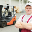 Warehouse worker in front of forklift — Stock Photo #6045192