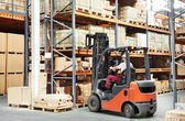 Worker driver at warehouse forklift loader works — Foto Stock