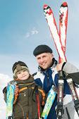 Leende son och far med skidor på vintern — Stockfoto
