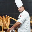 Arab chef cutting bread - Stock Photo