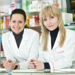 Two Pharmacy chemist women in drugstore — Zdjęcie stockowe #6494622