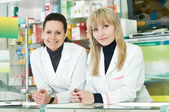 Two Pharmacy chemist women in drugstore — Stock Photo