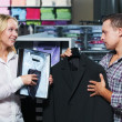 Stock Photo: Young couple at clothes shopping