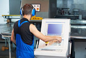 Worker operating cnc punch press — Stock Photo