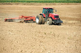 Ploughing tractor at field cultivation work — Stock Photo