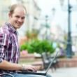 Smiling man with laptop — Stock Photo