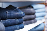 Jeans clothes on shelf in shop — Stok fotoğraf