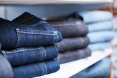 Jeans kleding op plank in winkel — Stockfoto