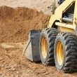 Stock Photo: Skid steer loader works