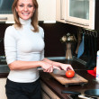 Beautiful happy smiling woman in kitchen interior cuts a tomato — Stock Photo