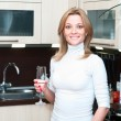 Beautiful happy smiling woman in kitchen interior drinking champagne — Stock Photo