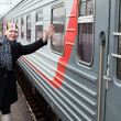 Girl says goodbye departing train and waves by hand after him - Foto Stock