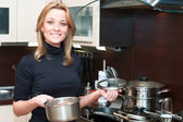 Beautiful happy smiling woman in kitchen interior with food in pan — Stock Photo