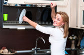 Beautiful happy smiling woman in kitchen interior — Stock Photo