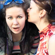 Young beautiful woman whispers something to girlfriend in her ear — Stock Photo