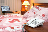 Bedroom interior with phone and laptop near bed on table — Stock Photo