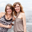 Two beautiful young women a Caucasians standing together on the deck - Stock Photo
