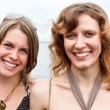 Stock Photo: Two beautiful young women standing together and smiling