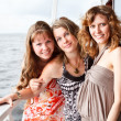 Three beautiful young women a Caucasians standing together on the deck of y — Stock Photo #6375691