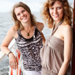 Two beautiful young women a Caucasians standing together on the deck of yac - Stock Photo