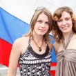 Stock Photo: Two Russian beautiful young females are standing under flag of Russia