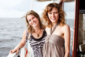 Two beautiful young women a Caucasians standing together on the deck of yac — Stock Photo