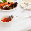 Plate with caviar  on table, cutlery for dinner, selective focus. - Stock Photo