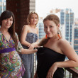 Three young Caucasian women standing on balcony of city high-rise building — Stock Photo