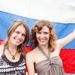 Foto Stock: Two Russian beautiful young women are standing under flag of Russia