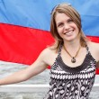 Foto Stock: One Russian beautiful young woman is standing under flag of Russia