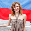 One Russian beautiful young woman is standing under flag of Russia - Stock Photo