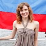 un russe belle jeune femme se tient debout sous le drapeau de la Russie — Photo