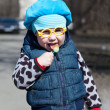 Little child with lollipop is standing outdoors. Funny glasses — 图库照片