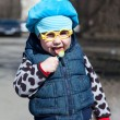 Little child with lollipop is standing outdoors. Funny glasses — Stock Photo