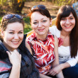 Portrait of three happy friends with a women smiling — Stock Photo #6489909