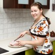 Beautiful happy smiling woman in kitchen interior with chicken — Stock Photo #6489936