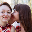 Young beautiful woman whispers something to girlfriend in her ear — Stock Photo #6489951