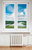 White plastic window with radiator under it. — Stock Photo