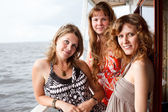 Three beautiful young women a Caucasians standing together on the deck — Stock Photo