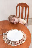 Little child sitting along at table with empty plate — Stock Photo