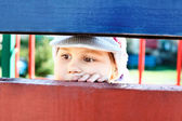 Little child looking through a crack between wooden planks — Stock Photo