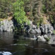 Fisherman sitting on the rocks in mountain river. — Stock Photo
