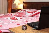 Laptop na stole w pobliżu łóżka w sypialni — Zdjęcie stockowe