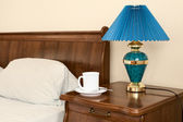 White cup and lamp on a bedside nightstand — Stock Photo