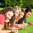 Stok fotoğraf: Teenage Female Friends Lying on Green at Park