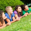 Teenage Female Friends Lying on Green at Park — Stock Photo #5767280